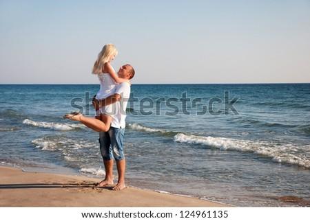 loving couple walking on the sea beach at summer - stock photo