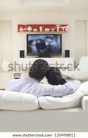 Loving couple watching TV while sitting on sofa - stock photo