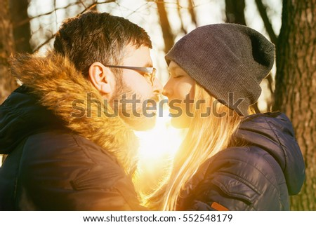 Loving couple with closed eyes is kissing outdoors at sunset background. Concept of Valentines Day