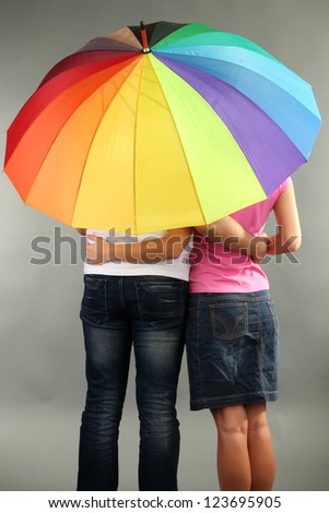 Loving couple with umbrella on grey background - stock photo