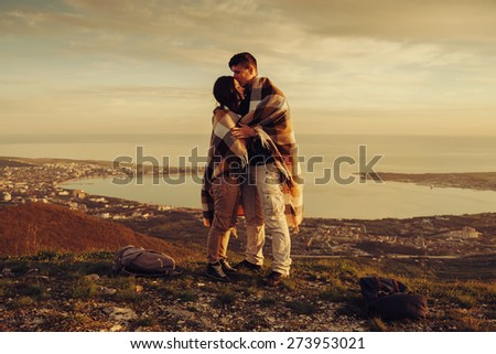 Loving couple wrapped in plaid standing on peak of mountain above bay at sunset - stock photo