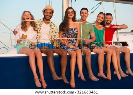 Loving couples relaxing on a yacht. Happy young people sailing on the yacht. Beautiful guys and girls spend the weekend on a yacht. Cruise on a yacht at sea. Party on a yacht. - stock photo