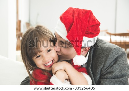 Loving dad kissing smiling daughter in Christmas - stock photo
