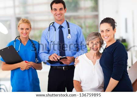 loving daughter accompanying her senior mother for check up in doctor's office - stock photo