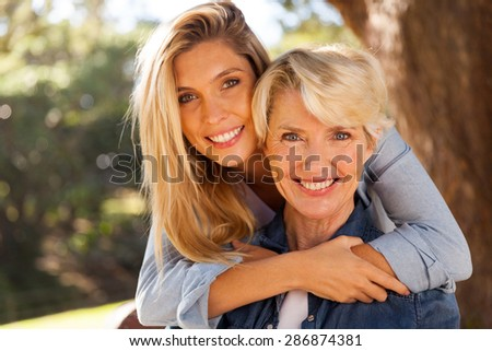 loving daughter hugging middle aged mother outdoors - stock photo