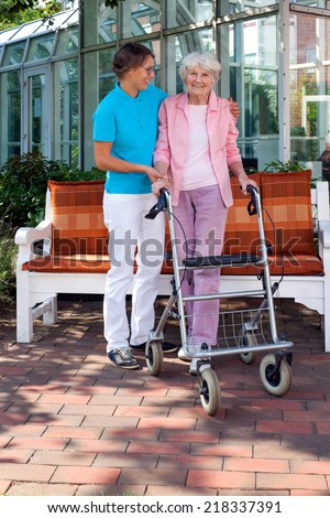 Loving daughter or care assistant helping her elderly mother as they enjoy a sunny day in the garden taking a walk with the use of a walking aid - stock photo