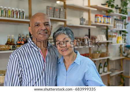 Loving elder couple at a healthy food store looking at the camera smiling