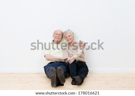 Loving elderly couple in their new home sitting side by side on the bare wooden floor smiling in satisfaction at having achieved their goal of a dream house - stock photo