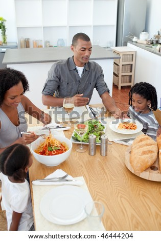 Loving family dining together in the kitchen - stock photo
