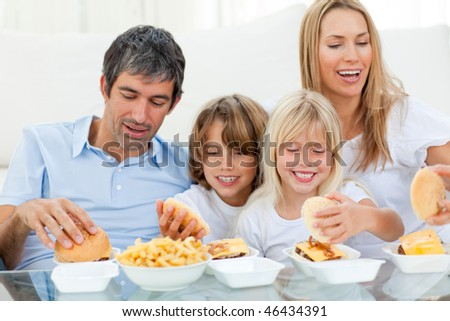 Loving family eating hamburgers sitting on sofa - stock photo