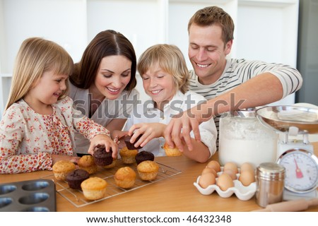 Loving family eating their muffins in the kitchen - stock photo