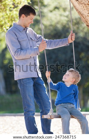 loving family of two having fun swinging in the park  - stock photo