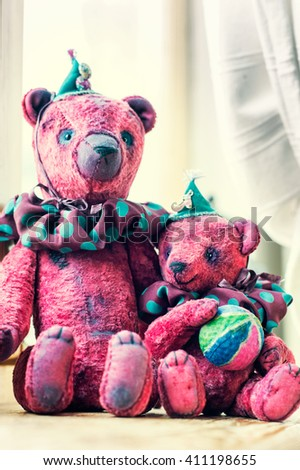 Loving family of two small vintage handmade textile sweet teddy bear art toys together. Indoors closeup vertical close up image with retro filter. - stock photo