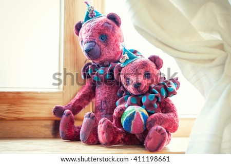 Loving family of two small vintage handmade textile sweet teddy bear art toys together. Indoors closeup horizontal close up image with retro filter. - stock photo