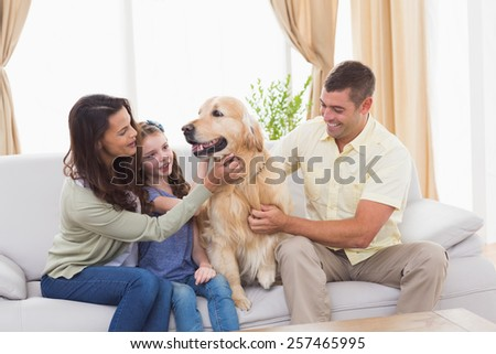 Loving family stroking dog while sitting on sofa at home - stock photo