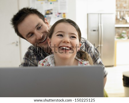 Loving father and daughter with laptop smiling together at home