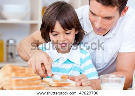 Loving father and his son spreading jam on bread in the kitchen