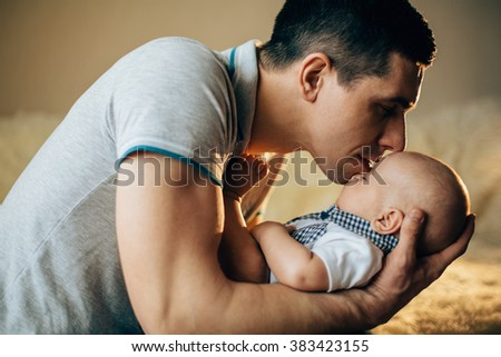 Loving father hand holding cute sleeping newborn baby child - stock photo