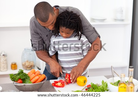 Loving father helping his son cut vegetables in the kitchen - stock photo