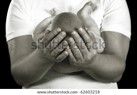 loving father holding infant daughter tenderly - stock photo