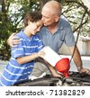 Loving father kisses his son as they work on the car engine together. - stock photo