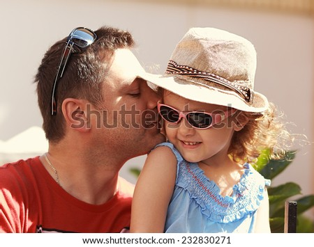 Loving father kissing his happy child girl in sun glasses on nature summer background - stock photo