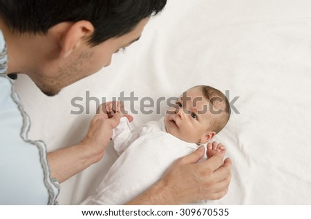 Loving father playing with his new born baby. Father holding baby's hands, looking at him with love. Parent love. - stock photo