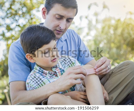 Loving Father Puts a Bandage on the Knee of His Young Son in the Park. - stock photo