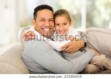 loving father sitting on the couch with his pretty daughter  - stock photo
