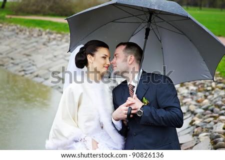 Loving gaze of bride and groom at the wedding walk - stock photo