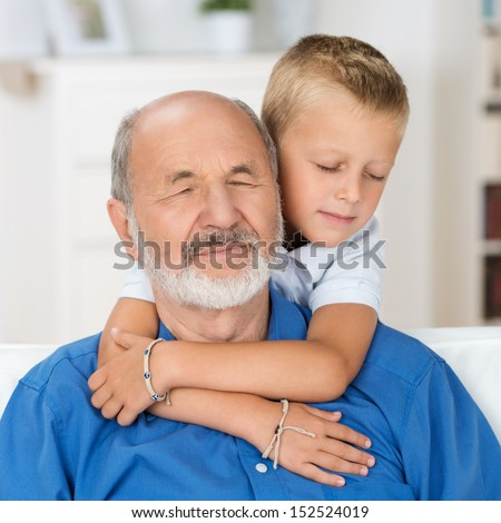 Loving grandfather with his eyes closed in love and appreciation as his adorable young grandson hugs him from behind with his arms around his neck - stock photo