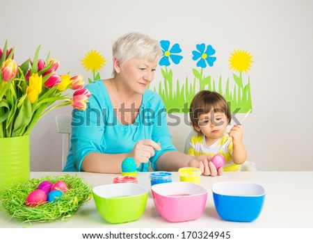 Loving grandma teaching her grandson to color eggs for Easter at home - stock photo
