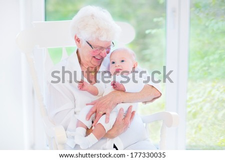 Loving grandmother singing a song to her newborn baby grandson sitting in a white rocking chair next to a big garden view window - stock photo