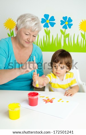 Loving grandmother teaching her grandson to draw with paint at home - stock photo