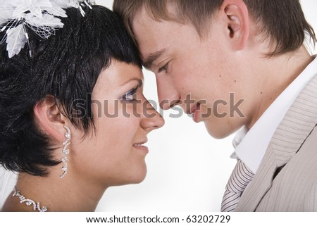 Loving groom and beautiful bride are happy together. A white background.