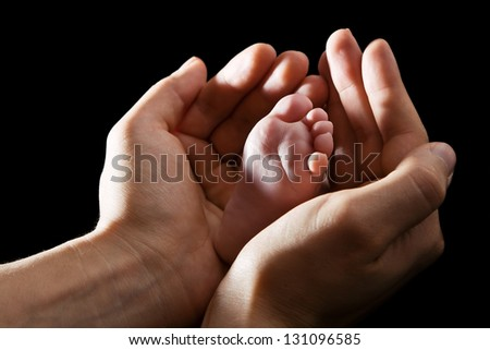 Loving hands gently embracing infant foot, black background - stock photo