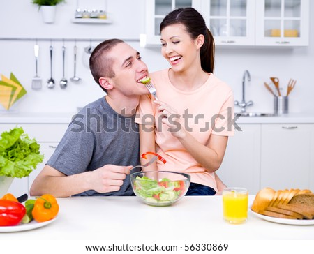Loving happy couple eating salad in the kitchen - indoors - stock photo
