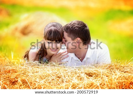 Loving happy couple having fun in a field on a haystack. Summer vacations concept. - stock photo