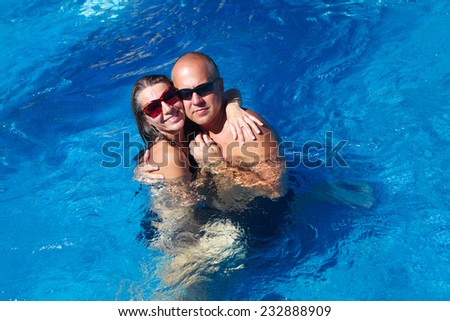Loving happy couple in pool. Summer vacation.