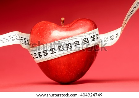loving healthy food. Heart shaped red apple with measuring tape - stock photo