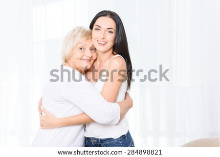 Loving hearts. Portrait of two women of different generations standing and hugging on white background - stock photo
