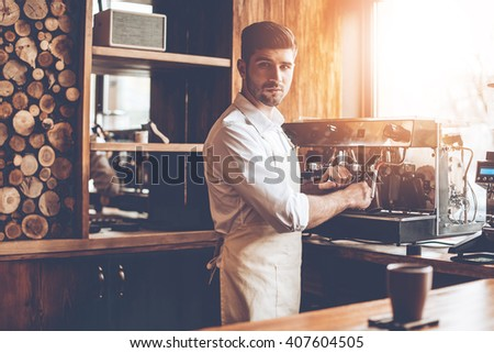 Loving his job. Young man in apron making coffee and looking at camera while standing at cafe - stock photo