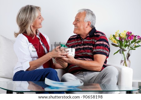 Loving husband giving gift to his wife - stock photo
