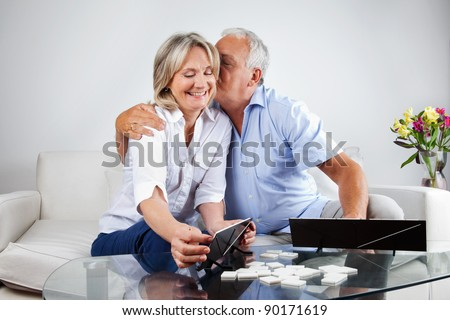 Loving husband kissing his wife while playing rummy at home. - stock photo