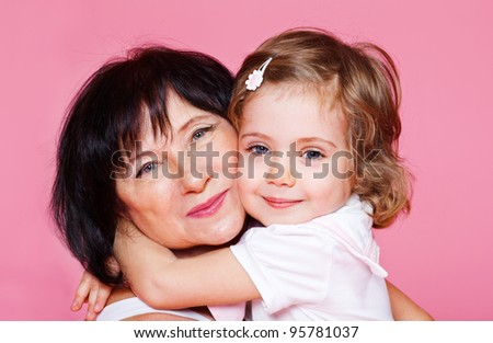 Loving kid embracing grandmother, over pink - stock photo