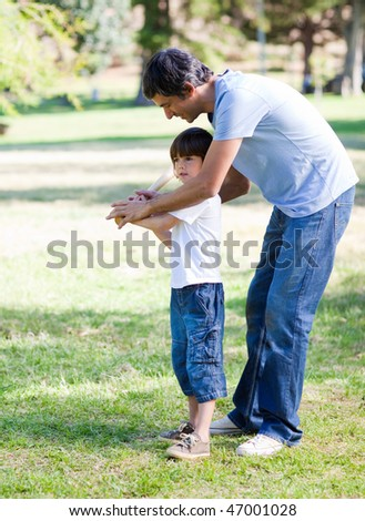 Loving little boy playing baseball with his father in the park - stock photo