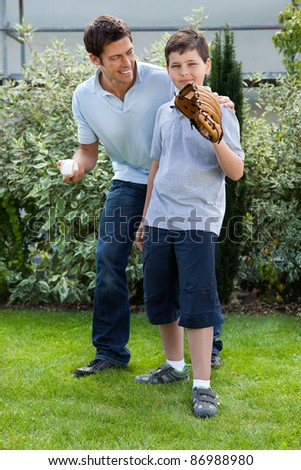 Loving little boy playing baseball with his father in their backyard - stock photo