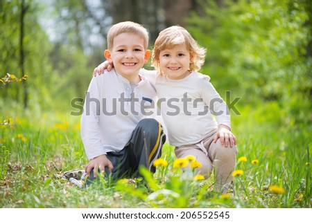 Loving little brother and sister at summer forest - stock photo