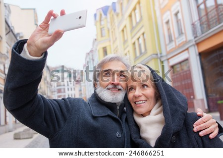 Loving mature caucasian couple taking selfie by mobile phone on city street - stock photo