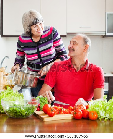 loving mature couple cooking with tomatoes in kitchen at home